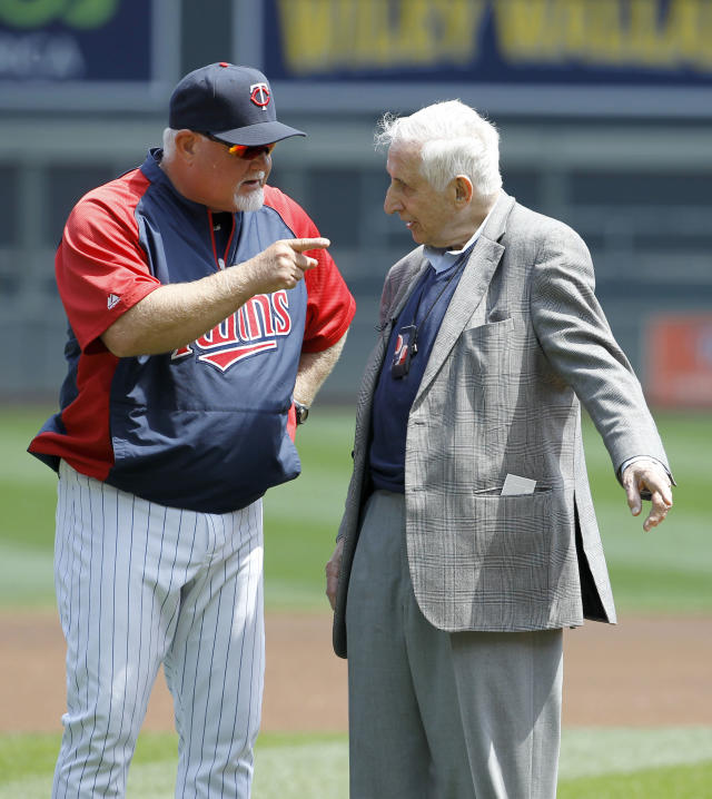 FILE - In this May 18, 2014, file photo, Star Tribune of Minneapolis sports columnist Sid Hartman, right, who turned 100 on Sunday, March 15, 2020, talks with Minnesota Twins manager Ron Gardenhire as Hartman was honored by the Twins organization before a baseball game against the Seattle Mariners in Minneapolis. (AP Photo/Ann Heisenfelt, File)
