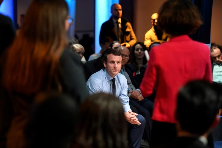 French presidential candidate  Emmanuel Macron listens to people during a campaign rally in the tough Paris suburb of Saint-Denis