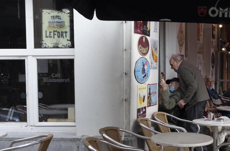 A elderly man is wheeled into a cafe in the historical center of Antwerp, Belgium, Sunday, Oct. 18, 2020. Faced with a resurgence of coronavirus cases, the Belgian government on Friday announced new restrictions to try to hold the disease in check, including a night-time curfew and the closure of cafes, bars and restaurants for a month. The measures will take effect on Monday, Oct. 19, 2020. (AP Photo/Virginia Mayo)