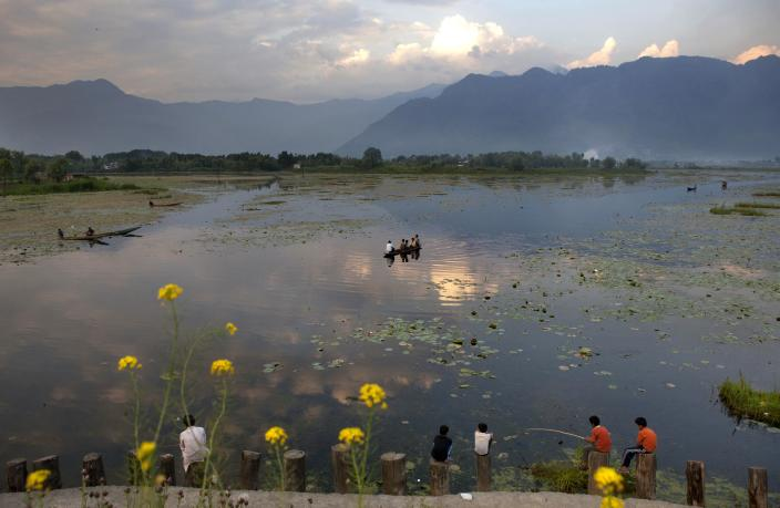 In this photo taken on Wednesday, May 13, 2012, Kashmiri Muslims fish on the shore of Nageen Lake on the outskirts of Srinagar, India. Traditional measures of economic progress like GDP are being criticized as inadequate for ignoring such downsides as pollution or diminishing resources from fresh water to fossil fuels. There is increased urgency to arguments for a more balanced and accurate reckoning of the costs, particularly as fast-developing nations such as India and China jostle with rich nations for access to those limited resources and insist on their right to pollute on a path toward economic development. (AP Photo/ Dar Yasin)