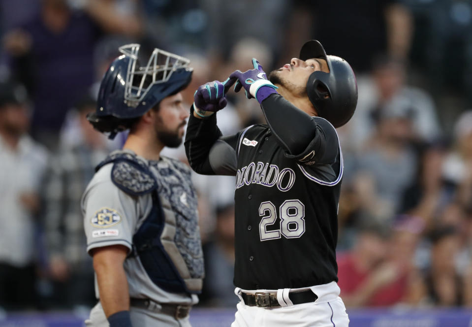 Colorado Rockies' Nolan Arenado gestures as he crosses home plate after hitting a two-run home run, next to San Diego Padres catcher Austin Hedges during the first inning of a baseball game Friday, Sept. 13, 2019, in Denver. (AP Photo/David Zalubowski)