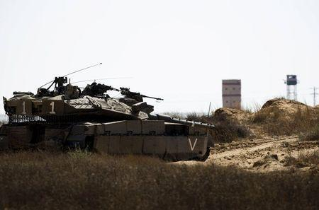 An Israeli army tank takes position along Israel's border with Egypt's North Sinai (seen in background) July 1, 2015. REUTERS/Amir Cohen