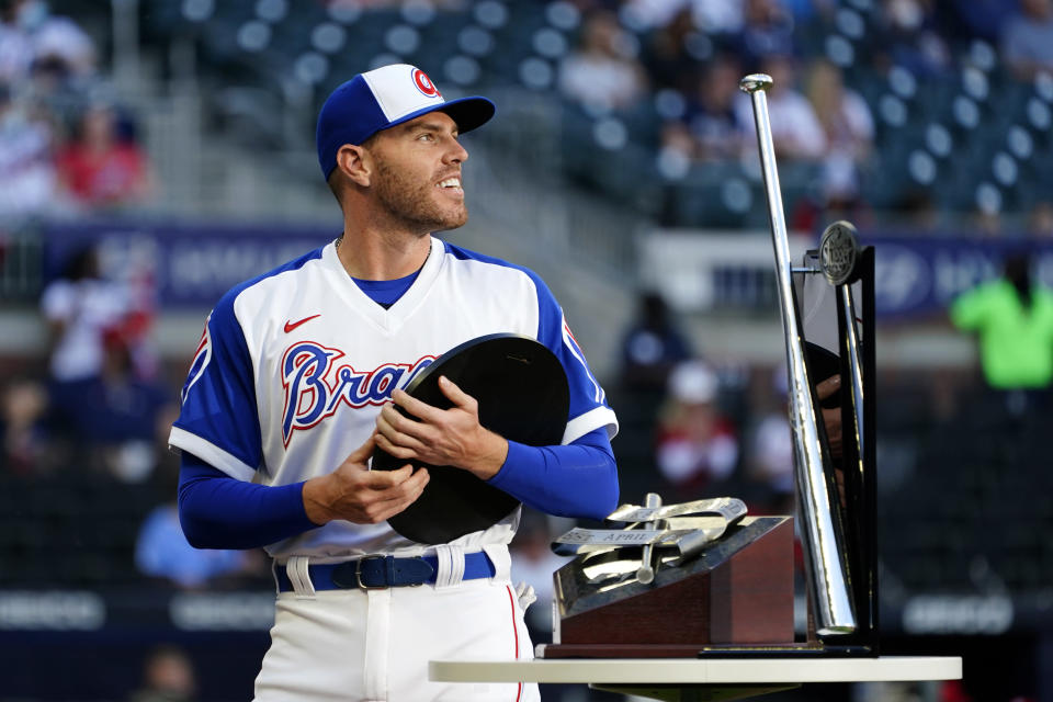 Atlanta Braves first baseman Freddie Freeman (5) holds the National League Most Valuable Player award during a ceremony before a baseball game against the Philadelphia Phillies Sunday, April 11, 2021, in Atlanta. (AP Photo/John Bazemore)
