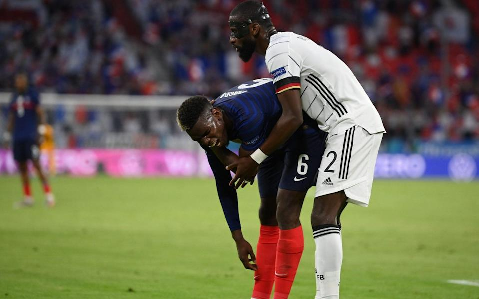 Paul Pogba winces in pain after his coming-together with Antonio Rudiger - REUTERS