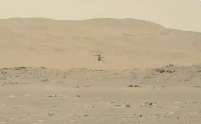 In this image from video made available by NASA, the Mars Ingenuity helicopter hovers above the surface of the planet during its second flight on Thursday, April 22, 2021. (NASA via AP)
