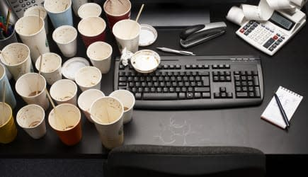 Empty coffee cups on office desk, high angle view