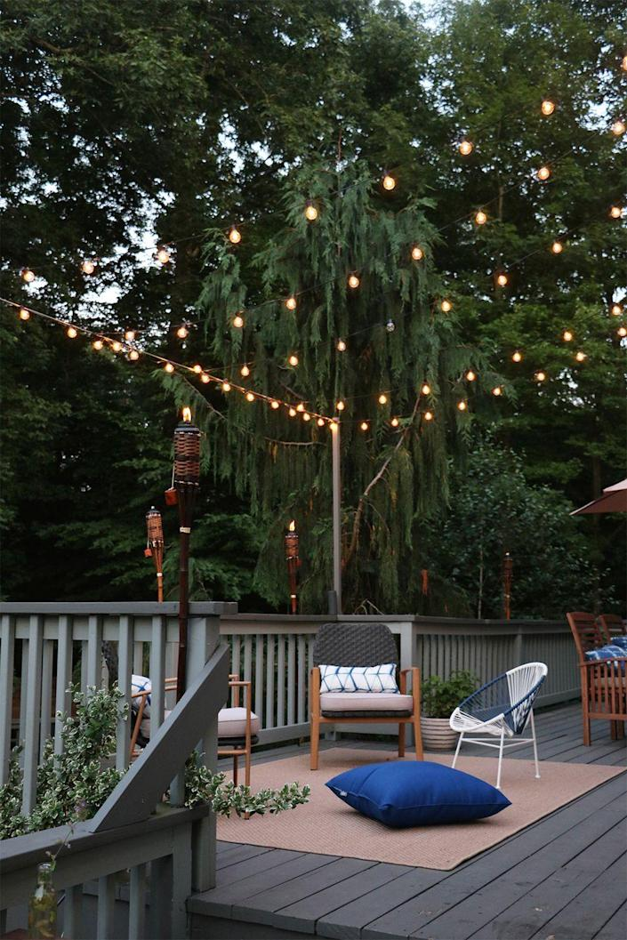"""<p>It's always a starry night when you hang string lights above your back patio. You'll want to wind down in this pleasant place every day of the week.</p><p><strong>See more at <a href=""""https://rootanddwell.com/blog/2018/7/5/how-we-hung-our-back-deck-string-lights-for-bistro-style-ambiance"""" rel=""""nofollow noopener"""" target=""""_blank"""" data-ylk=""""slk:Root + Dwell"""" class=""""link rapid-noclick-resp"""">Root + Dwell</a>.</strong></p><p><a class=""""link rapid-noclick-resp"""" href=""""https://www.amazon.com/Backyard-Hanging-Outdoor-Pergola-Deckyard/dp/B00RQHBZVS/ref=sr_1_12?tag=syn-yahoo-20&ascsubtag=%5Bartid%7C10050.g.3404%5Bsrc%7Cyahoo-us"""" rel=""""nofollow noopener"""" target=""""_blank"""" data-ylk=""""slk:SHOP STRING LIGHTS"""">SHOP STRING LIGHTS</a></p>"""