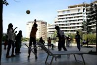 The anxiety of the adults chimes awkwardly with the sound of children playing ball games or jumping into the pool (AFP/Gent SHKULLAKU)