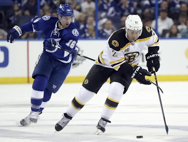 Boston Bruins right wing Jarome Iginla (12) avoids a hook by Tampa Bay Lightning right wing Teddy Purcell (16) as he skates up the ice during the first period of an NHL hockey game Saturday, Oct. 19, 2013, in Tampa, Fla. (AP Photo/Chris O'Meara)