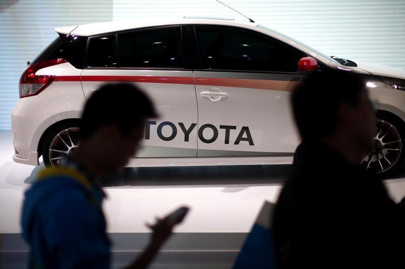 People look at a Toyota car during the 15th Shanghai International Automobile Industry Exhibition in Shanghai