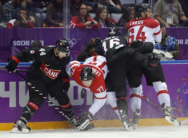 Canada defenseman Marc-Edouard Vlasic (44), Austria forward Brian Lebler (77), Canada forward Jonathan Toews (16) and Austria defenseman (64) get tangled up on the boards in the second period of a men's ice hockey game at the 2014 Winter Olympics, Friday, Feb. 14, 2014, in Sochi, Russia. (AP Photo/Mark Humphrey)