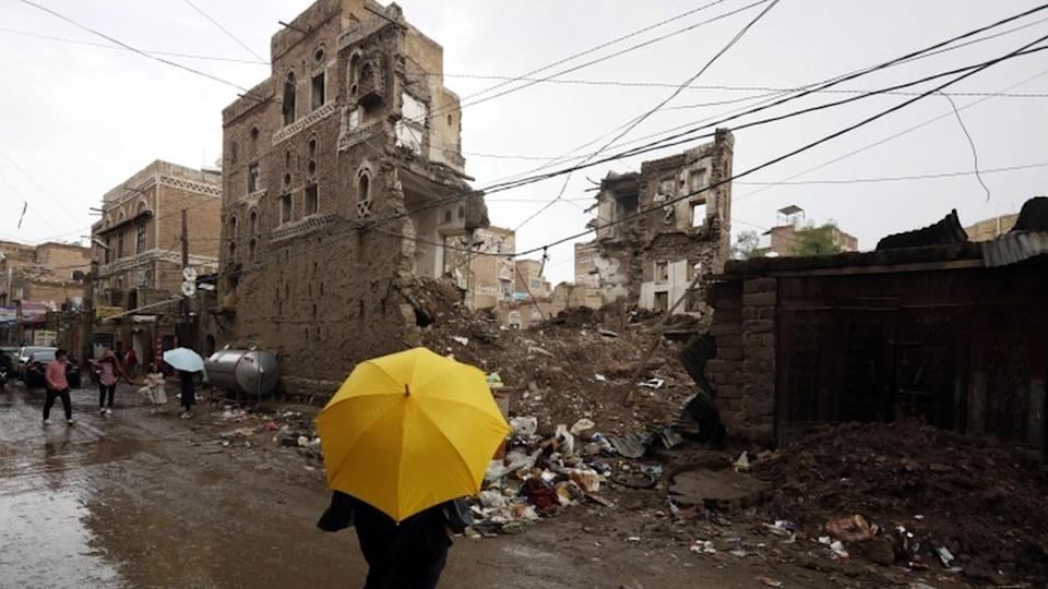 A Yemeni holding a yellow umbrella stands in front of a collapsed building in Sanaa