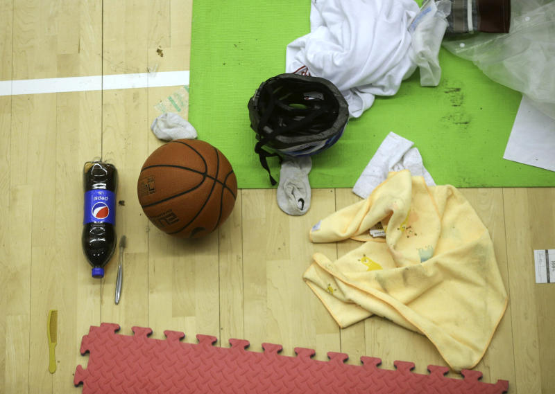 Clothes and a basketball belonging to protesters are left in the campus of the Polytechnic University in Hong Kong, Wednesday, Nov. 20, 2019. A small group of protesters refused to leave Hong Kong Polytechnic University, the remnants of hundreds who took over the campus for several days. They won't leave because they would face arrest. Police have set up a cordon around the area to prevent anyone from escaping. (AP Photo/Ahmad Ibrahim)