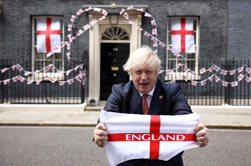 Boris Johnson poses at Downing Street with a flag ahead of the Euro 2020 final (REUTERS)