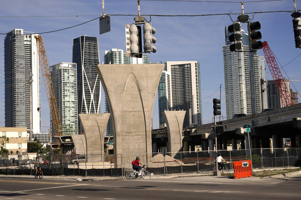 Columns for the new Signature Bridge are in place with the Miami skyline in the background, Friday, April 9, 2021, in the Overtown neighborhood of Miami. At right is the original Interstate 395 bridge built in the 1960's which forced out thousands of residents. The Signature Bridge project coincides with the revitalization of the neighborhood that is currently underway. Community leaders are working to ensure that Overtown's Black history and culture are preserved in the process. (AP Photo/Lynne Sladky)