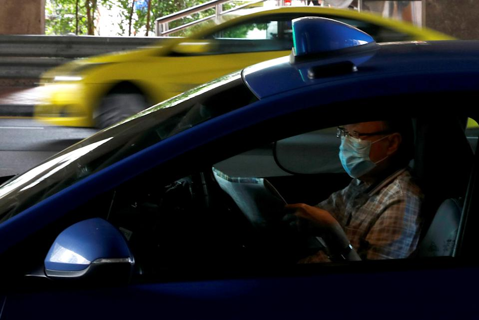 LTA cited the example of a parent being allowed to travel with his or her two children in the same taxi or PHC during the Phase 2 (Heightened Alert) period. (PHOTO: Reuters)
