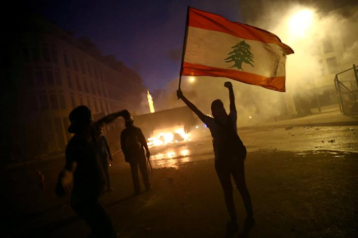 A demonstrator holds a Lebanese flag as another hurls stones during a protest: REUTERS