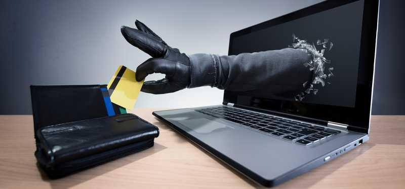 Gloved hand reaches through laptop screen a steals a credit card.