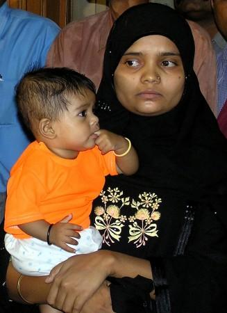 Bilkis Yakub Rasool, holds her six-month-old daughter Fatima, during a news conference in the western Indian city of Ahmedabad, August 8, 2004.