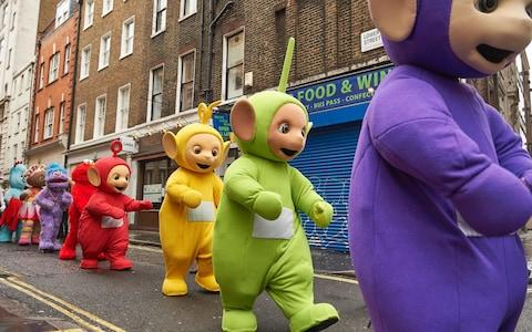 Performers dressed as children's toys and characters from television shows, including the Teletubbies, prepare to participate in the Hamleys Christmas Toy Parade on Regent Street in London - Credit: AFP