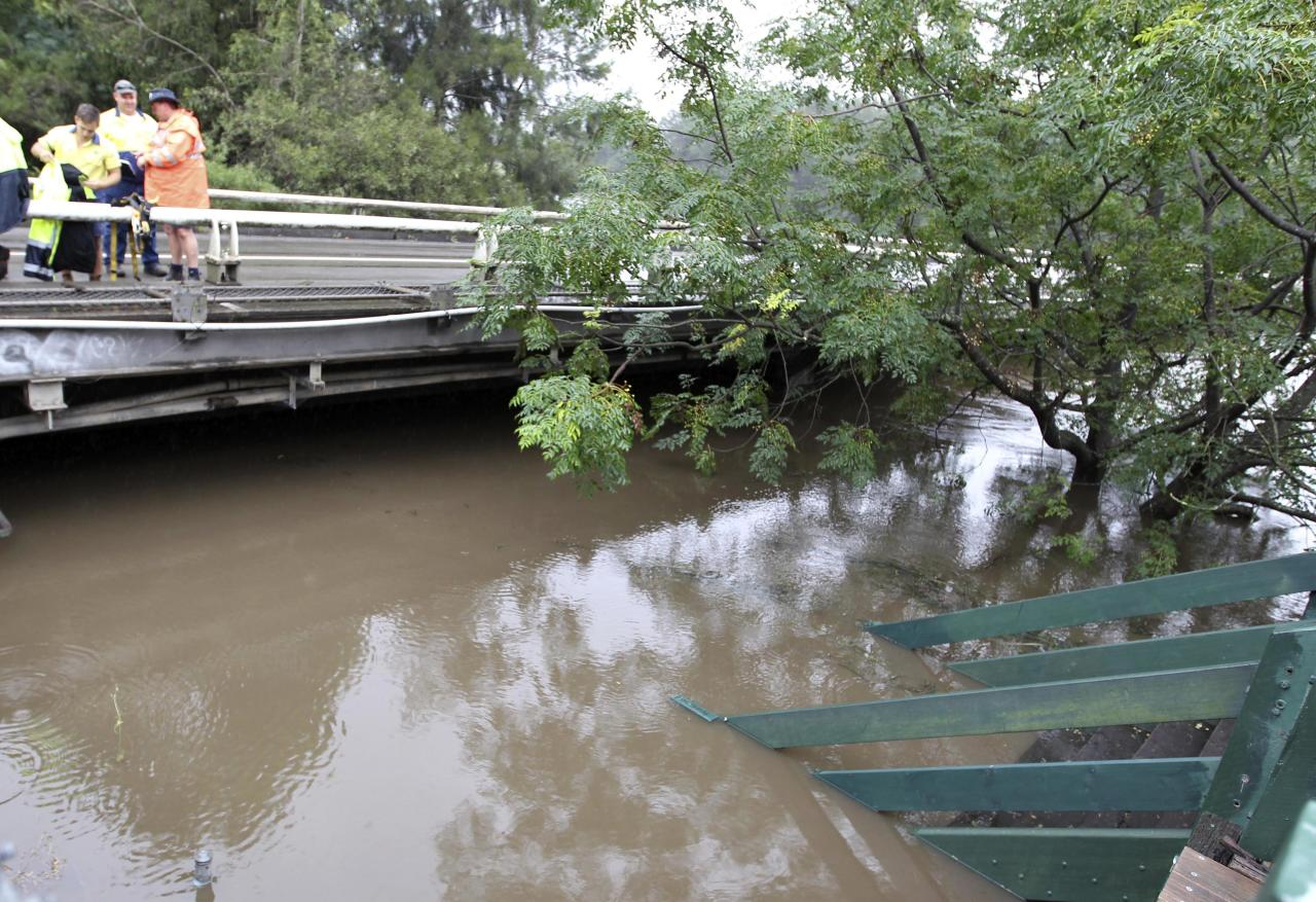 State emergency workers standing on a bridge in the Sydney suburb of Windsor watch rising waters as it covers a walkway under the Windsor Bridge on the Hawkesbury River after the flood gate of the Warragamba Dam were opened in Sydney, Australia, Saturday, March 3, 2012. Around 3,500 people have been told to evacuate from their homes across New South Wales as 75 percent of the state is affected by floodwaters. (AP Photo/Rob Griffith)