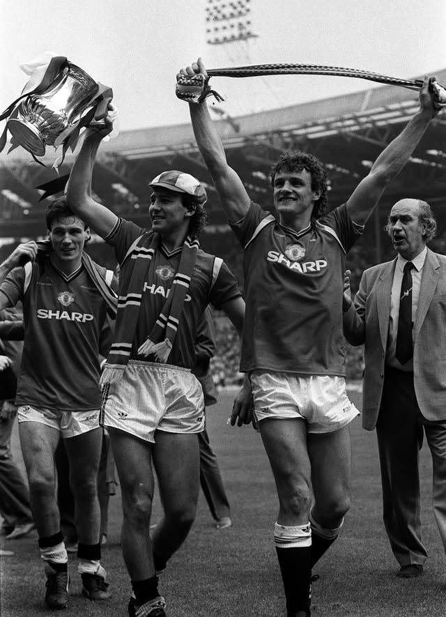 Manchester United captain Bryan Robson shows off the FA Cup after beating Everton in 1985 (PA)