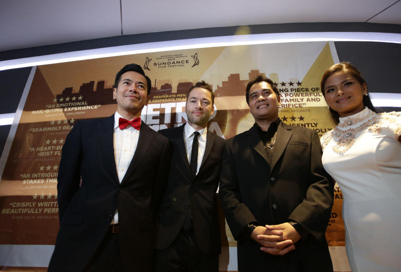 """In this Thursday Oct.3, 2013 photo, Briton Sean Ellis, second from left, writer-director of """"Metro Manila"""" - Britain's nominee to the Oscar Awards' best foreign language film, poses with his actors, from left, Jake Macapagal, John Arcilla and Althea Vega, prior to the premier screening at a cinema in Taguig city, east of Manila, Philippines. The film features an all-Filipino cast and a story that traces the sacrifices and hopes of an impoverished family from the countryside that tries its luck in the dark and squalid ghettos of the Philippine capital Manila. """"Metro Manila,"""" is one of three foreign language films nominated to the Oscar best foreign language category which delves into the lives of Filipinos. Movie industry players say it could be a signal of a new emergence of Philippine cinema. (AP Photo/Bullit Marquez)"""