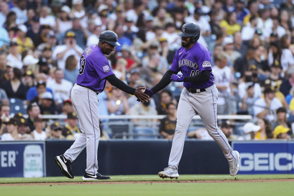 Colorado Rockies' German Marquez celebrates with third base coach Stu Cole after hitting a home run against the San Diego Padres during the fifth inning of a baseball game Saturday, July 31, 2021, in San Diego. (AP Photo/Derrick Tuskan)