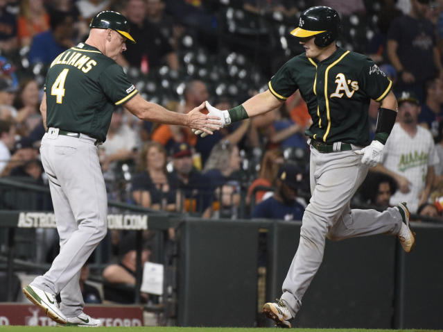 Oakland Athletics' Sean Murphy, right, shakes hands with third base coach Matt Williams after hitting a solo home run off Houston Astros relief pitcher Josh James during the sixth inning of a baseball game, Wednesday, Sept. 11, 2019, in Houston. (AP Photo/Eric Christian Smith)