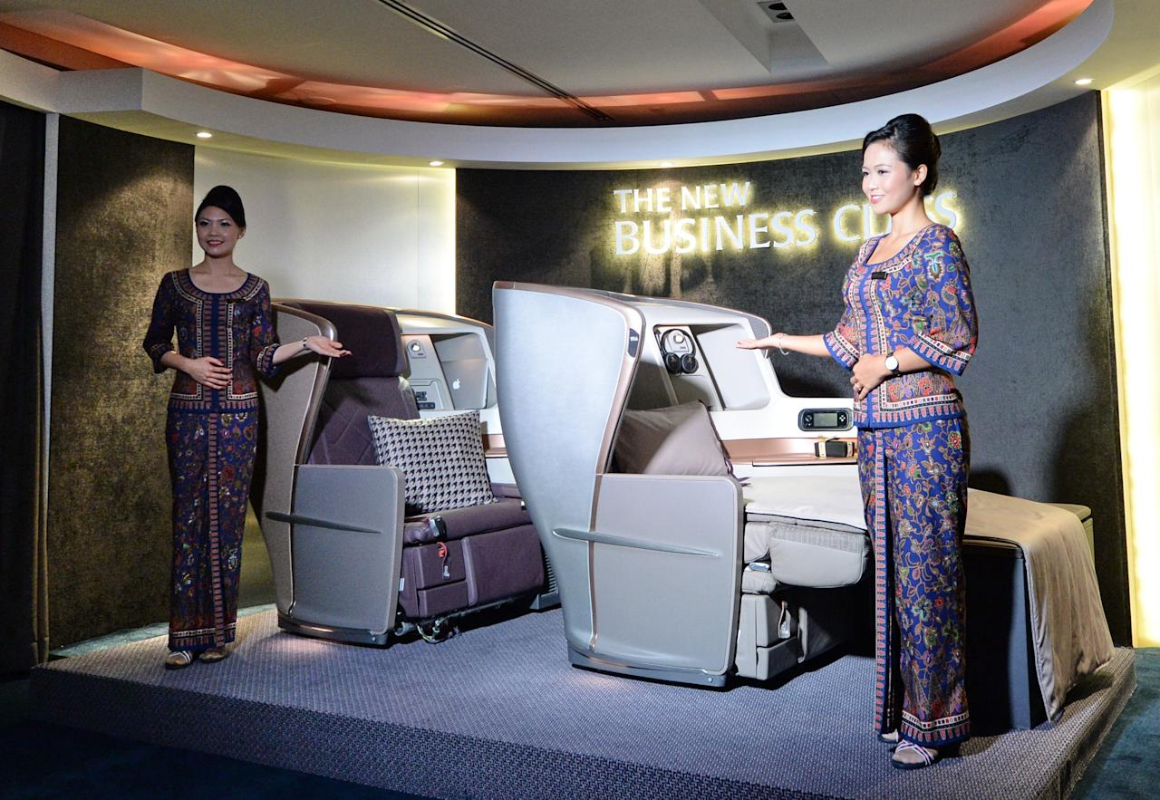 A Singapore Airlines (SIA) stewardesses stand next to a display of the new Singapore Airlines Business Class seats during their next generation cabin product launch in Singapore on July 9, 2013. SIA on July 9 unveiled new seats and other in-flight amenities as part of a sweeping upgrade of its cabins amid intensifying competition in the industry. AFP PHOTO / ROSLAN RAHMAN