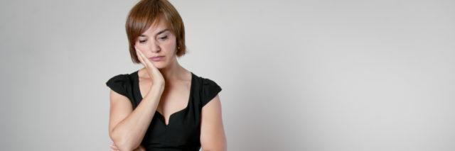 worried woman with brown hair standing over a table about to set it with her hand on her face staring blankly