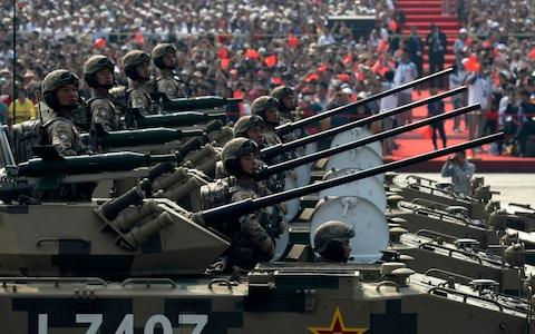 Military vehicles roll down during a parade to commemorate the 70th anniversary of the founding of Communist China - Credit: AP Photo/Ng Han Guan