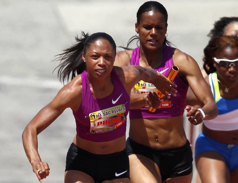 """Allyson Felix, left, gets the baton from Ginnie """"Powell"""" Crawford, right, to run the second leg of the women's 4x100-meter relay invitational elite for the Kersee All-Stars at the 2011 Mt. SAC Relays at Mt. San Antonio College, Saturday, April 16, 2011, in Walnut, Calif. (AP Photo/Danny Moloshok)"""