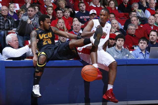 DAYTON, OH - JANUARY 22: Dyshawn Pierre #21 of the Dayton Flyers and Jordan Burgess #20 of the VCU Rams crash into a courtside table during the first half of the game at UD Arena on January 22, 2014 in Dayton, Ohio. (Photo by Joe Robbins/Getty Images)