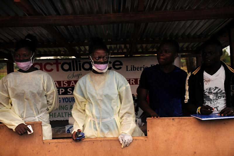 Sierra Leone health officials check passengers transiting at the border crossing with Liberia in Jendema, Sierra Leone on March 28, 2015