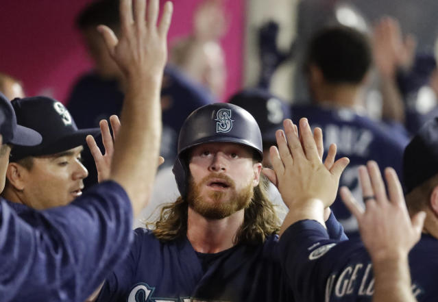 Seattle Mariners' Ben Gamel celebrates in the dugout after scoring on a sacrifice fly by Dee Gordon during the second inning of a baseball game in Anaheim, Calif., Thursday, Sept. 13, 2018. (AP Photo/Chris Carlson)