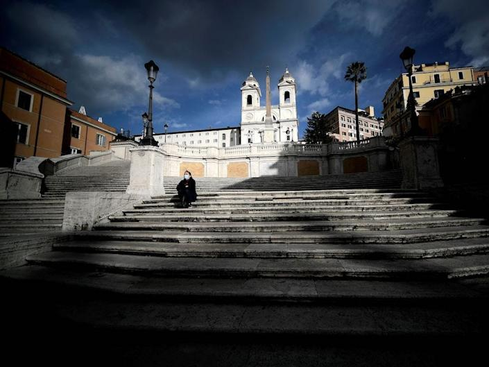 A face masked woman sits on empty Spanish Steps in downtown Rome on December 5, 2020.