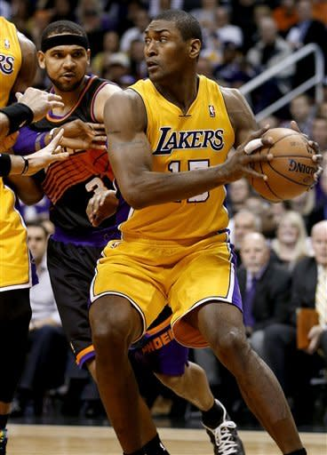 Los Angeles Lakers' Metta World Peace drives the baseline against Phoenix Suns' Jared Dudley during the first half of an NBA basketball game, Wednesday, Jan. 30, 2013, in Phoenix. (AP Photo/Matt York)