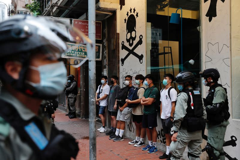 Riot police stop and search people during a march against national security law at the anniversary of Hong Kong's handover to China from Britain in Hong Kong