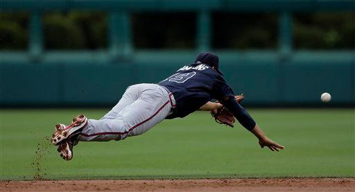 Atlanta Braves shortstop Andrelton Simmons cannot reach a single by Philadelphia Phillies' Carlos Ruiz in the second inning of a baseball game on Sunday, July 8, 2012, in Philadelphia. (AP Photo/Matt Slocum)