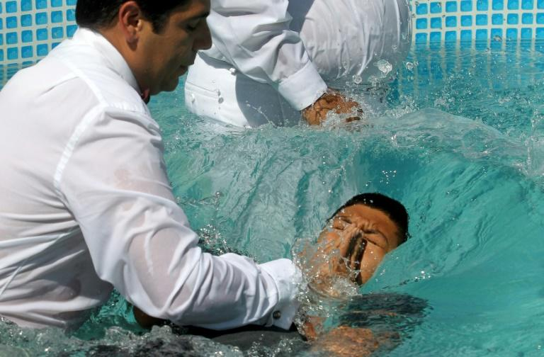"""Do you believe in Jesus Christ?"" a minister asked newly baptized members, who responded ""Amen!"" with their right hands raised before being plunged into the full-body baptismal pools (AFP Photo/Ulises Ruiz)"