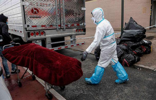 PHOTO: A man in a Hazmat suit transports a deceased body on a stretcher outside a funeral home in Brooklyn on April 30, 2020 in New York City. (Johannes Eisele/AFP via Getty Images)