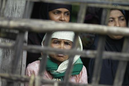 Rohingya Muslim women look out from their home at Aung Mingalar quarter in Sittwe
