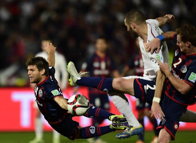 Real Madrid's French forward Karim Benzema (2nd from R) vies for the ball against San Lorenzo's defenders Walter Kannemann (L) and Mauro Cetto during their FIFA Club World Cup final football match in Marrakesh on December 20, 2014 (AFP Photo/Javier Soriano)