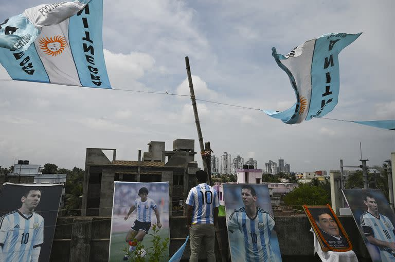A member of an Argentina's national football team fan club stands amid pictures of Argentina's captain Leo Messi (center R) and the late Argentine football legend Diego Maradona (center L) in a rooftop ahead of the Copa America final match between Argentina and Brazil, in Kolkata on July 10, 2021. (Photo by Dibyangshu SARKAR / AFP)