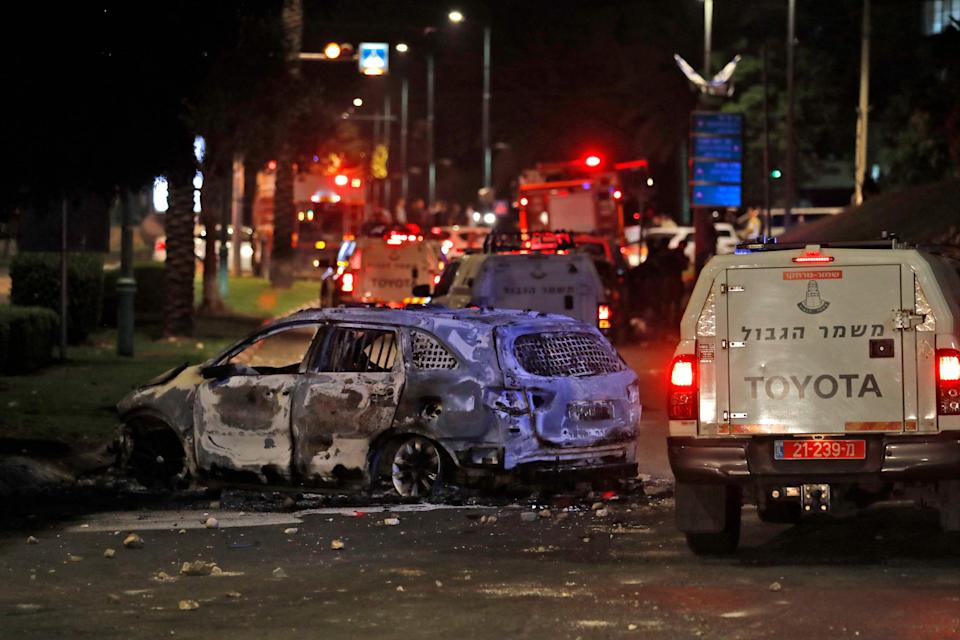 Israeli border police vehicles drive past an extinguished burnt vehicle in Lod near Tel Aviv (AFP via Getty Images)