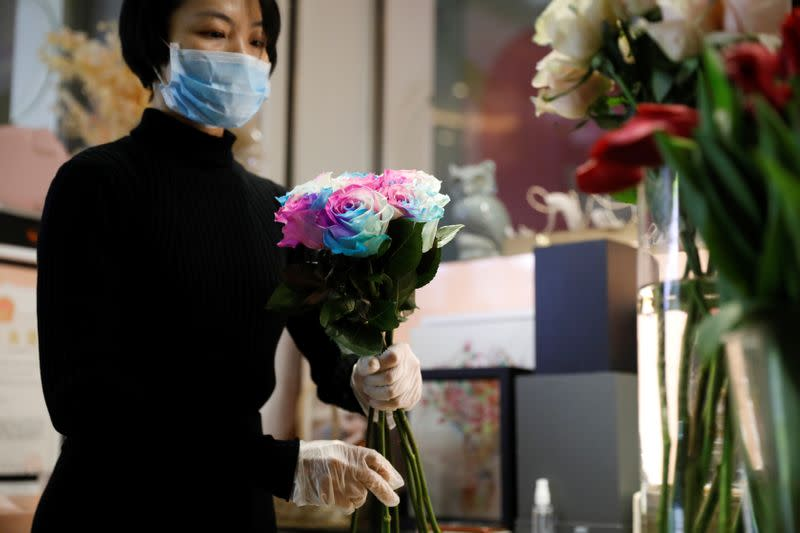 A florist who prefers to be called Cai Xiaoman wearing a face mask and gloves, ensembles a bouquet at a flowers shop in a shopping mall, as the country is hit by an outbreak of the new coronavirus, in Beijing