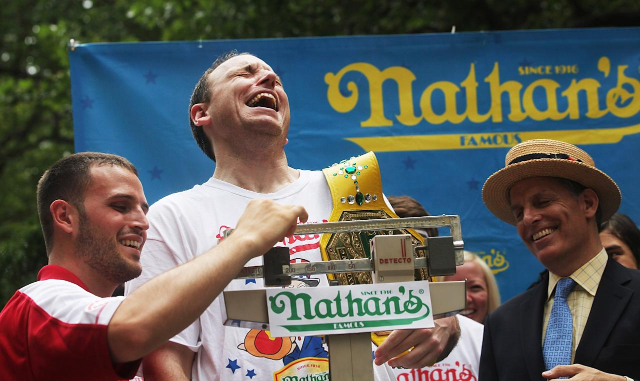NEW YORK, NY - JULY 03: Men's world record holder Joey Chestnut (C) laughs as he is weighed at the Nathan's Famous Fourth of July International Hot Dog Eating Contest weigh-in ceremony on July 3, 2013 in the Brooklyn borough of New York City. The annual hot dog eating event is expected to draw up to 40,000 fans on July 4, in the Coney Island section of Brooklyn. (Photo by Mario Tama/Getty Images)