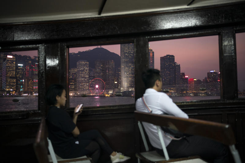 In this Oct. 10, 2019 photo, people ride in a ferry from Hong Kong Island to Kowloon as the sun sets in Hong Kong. The body-blow of months of political protests on Hong Kong's tourism is verging on catastrophic for one of the world's great destinations. Geared up to receive 65 million travelers a year, the city's hotels, retailers, restaurants and other travel-oriented industries are suffering. But some intrepid visitors came specifically to see the protests and are reveling in deep discounts and unusually short lines at tourist hotspots. (AP Photo/Felipe Dana)