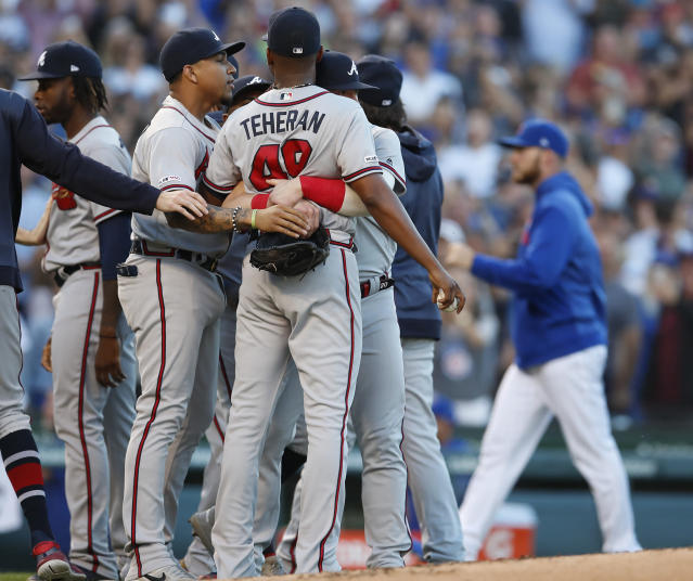 Atlanta Braves' Julio Teheran, center, is held back by Braves' Johan Camargo, second left, as the benches empty during a brief argument with the Chicago Cubs during the second inning of a baseball game Monday, June 24, 2019, in Chicago. (AP Photo/Jim Young)